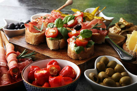 Italian antipasti wine snacks set. Cheese variety, Mediterranean olives, pickles, Prosciutto di Parma, tomatoes, artichokes and wine in glasses