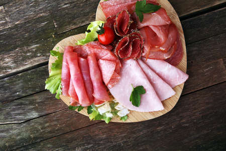 Food tray with delicious salami, pieces of sliced ham, sausage, tomatoes, salad and vegetable - Meat platter with selection Stock Photo - 93952859