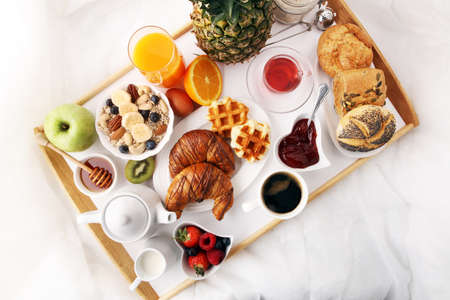 breakfast in bed with fruits and pastries on a tray -waffles, croissants, coffe and juice