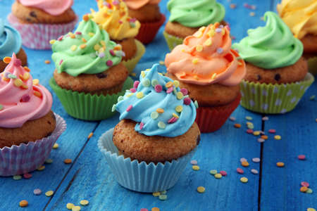 Tasty cupcakes on wooden background. Birthday cupcake in rainbow colors