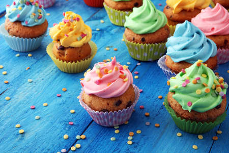 Tasty cupcakes on wooden background. Birthday cupcake in rainbow colors 版權商用圖片 - 95171289