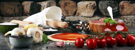 Fresh original Italian raw pizza preparation with fresh ingredients.