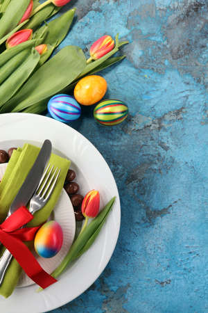 Festive table setting for Easter with fork, knife and tulip