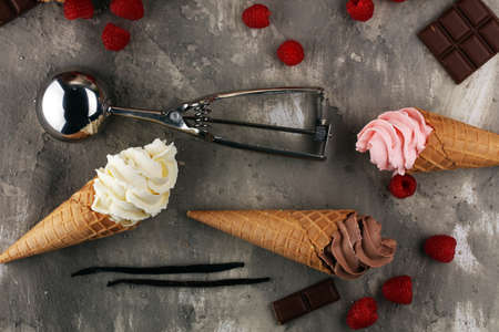 Vanilla frozen yogurt or soft ice cream in waffle cone and strawberry, raspberry and chocolate softice cream Banque d'images