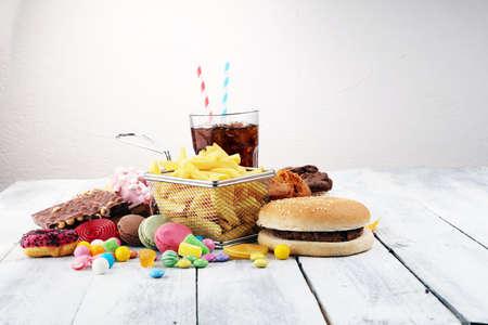 Niezdrowe produkty. jedzenie jest szkodliwe dla sylwetki, skóry, serca i zębów. Asortyment żywności szybkowęglowodanowej.
