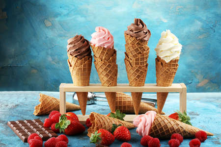 Vanilla frozen yogurt or soft ice cream in waffle cone and strawberry, raspberry and chocolate softice cream Banque d'images - 97666386