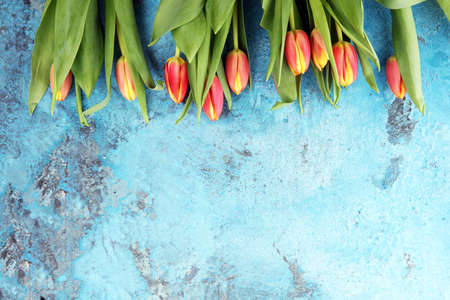 Festive setting for Easter with beautiful tulips on blue background