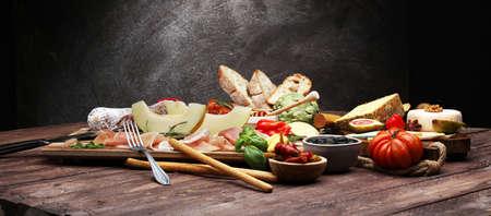 Set de aperitivos de vino italiano antipasti. Variedad de queso, aceitunas mediterráneas, encurtidos, jamón serrano con melón, salami y vino en copas sobre fondo negro grunge