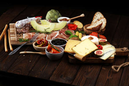 Italian antipasti wine snacks set. Cheese variety, Mediterranean olives, pickles, Prosciutto di Parma with melon, salami and wine in glasses over black grunge background