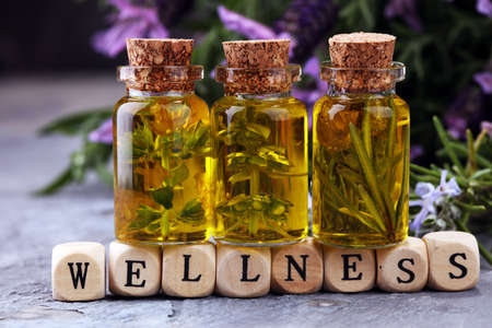 lavender oil in a glass bottle on a background of fresh flowers andWellness sign with wooden cubes
