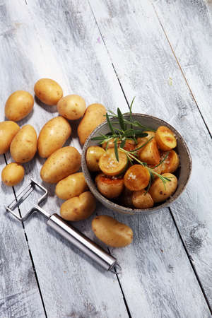Roasted potato with fresh rosemary in a bowl on rustic background