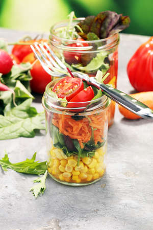Homemade salad in glass jar with vegetables. Healthy food, diet, detox, clean eating and vegetarian concept.
