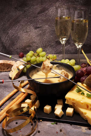 Gourmet Swiss fondue dinner on a winter evening with assorted cheeses on a board alongside a heated pot of cheese fondue with two forks dipping bread Stock Photo