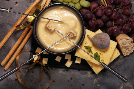 Gourmet Swiss fondue dinner on a winter evening with assorted cheeses on a board alongside a heated pot of cheese fondue with two forks dipping bread Foto de archivo