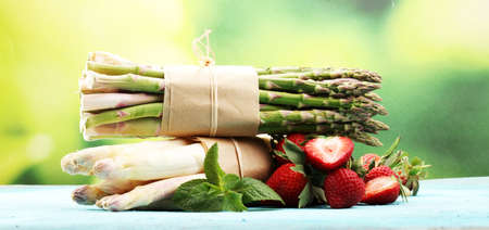 White and green fresh asparagus with a bunch of healthy strawberries Stock Photo