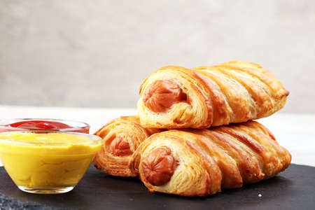 Delicious homemade sausage rolls on a black serving platter.