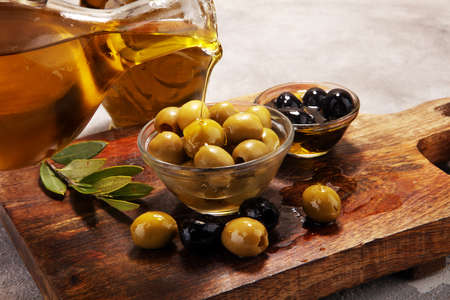 Bottle virgin olive oil and oil in a bowl with some olives.