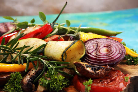 Grilled vegetables. Tomatoes, zucchini, bell pepper and fresh herbs. Vegan grill concept.