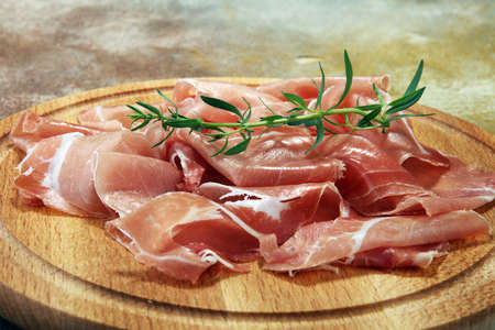 Italian prosciutto crudo or jamon with parsley. Raw ham.