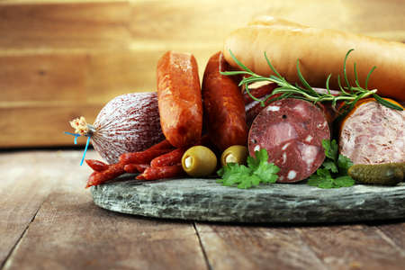 Food tray with delicious salami, ham,  fresh sausages, cucumber and herbs. Meat platter with selection Stock Photo - 103762671