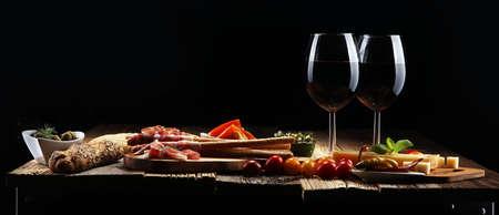 Italian antipasti wine snacks set. Cheese variety, Mediterranean olives, crudo, Prosciutto di Parma, salami and wine in glasses over wooden grunge background Stockfoto