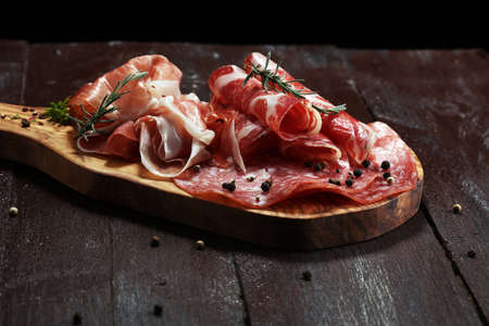 Food tray with delicious salami, coppa,  fresh sausages and herbs. Meat platter with selection.