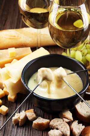 Gourmet Swiss fondue dinner on a winter evening with assorted cheeses on a board alongside a heated pot of cheese fondue with two forks dipping bread and white wine behind in a tavern or restaurant Stock Photo