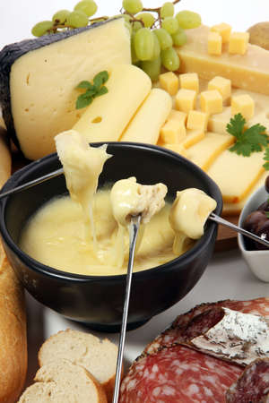 Gourmet Swiss fondue dinner on a winter evening with assorted cheeses on a board alongside a heated pot of cheese fondue with two forks dipping bread and white wine behind in a tavern or restaurant Foto de archivo