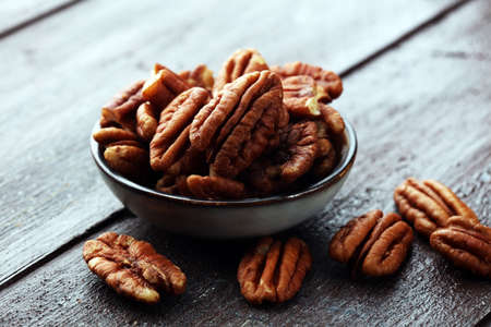 Pecan nuts on a rustic wooden table and pecan nuts in bowl.