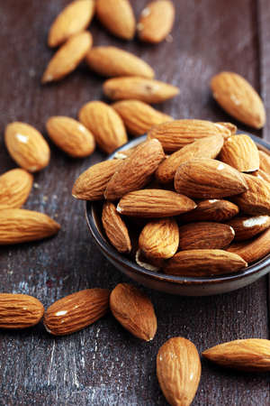 Almonds on a rustic wooden table and almond in bowl 스톡 콘텐츠