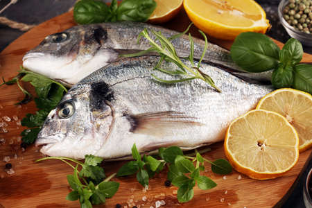 Delicious fresh fish. Fish with aromatic herbs, spices and vegetables - healthy food, diet or cooking concept Standard-Bild