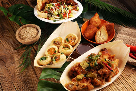 various street food with pani puri, chicken wings and coxinha on rustic background. balinese nasi campur and indian and brasilian street food Stock Photo