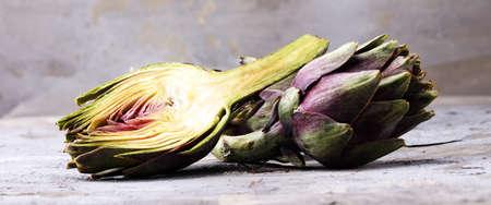 Artischocken auf grauem Hintergrund. frische Bio-Artischockenblume Standard-Bild