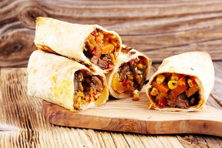 Burritos wraps with beef and vegetables on wooden background. Beef burrito, mexican food. 写真素材