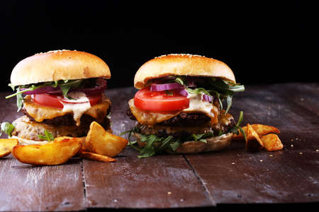 Tasty fresh meat burgers with salad and cheese and potato wedges. Homemade angus burger