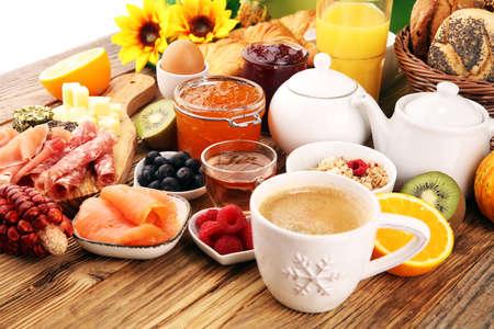 Frühstück auf dem Tisch mit Brötchen, Croissants, Kaffee und Saft Standard-Bild