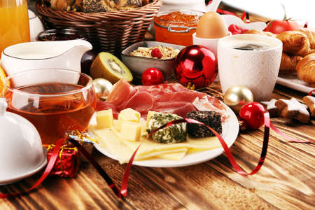 breakfast on table with bread buns, croissants, coffe and juice on christmas day. xmas holiday morning