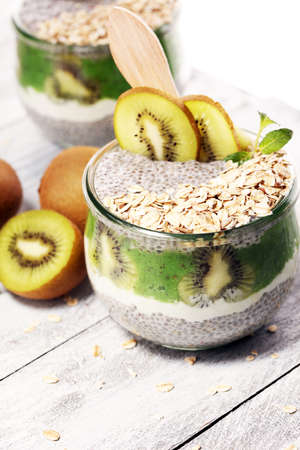 Healthy breakfast. chia pudding with kiwi and granola in glass on rustic background