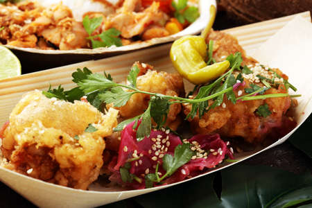 various street food with chicken wings on rustic background. balinese nasi campur and indian and brasilian street food