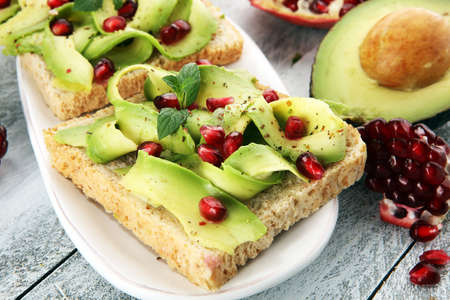 sliced avocado and ripe pomegranates on toast bread with spices and avocado