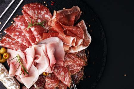 Marmorschneidebrett mit Schinken, Speck, Salami und Würstchen auf hölzernem Hintergrund. Fleischplatte