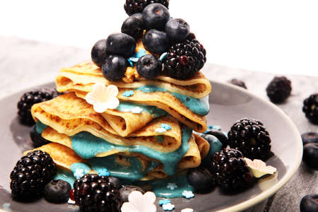Delicious Tasty Homemade crepes or pancakes with blackberries,blueberries and blue spirulina nicecream