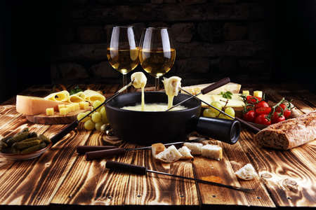 Gourmet Swiss fondue dinner on a winter evening with assorted cheeses on a board alongside a heated pot of cheese fondue with two forks dipping bread and white wine behind in a tavern or restaurant 스톡 콘텐츠