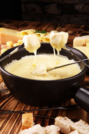 Gourmet Swiss fondue dinner on a winter evening with assorted cheeses on a board alongside a heated pot of cheese fondue with two forks dipping bread in a tavern or restaurant