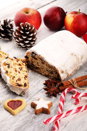 Traditional European Christmas pastry, fragrant home baked stollen, with spices and dried fruit. Sliced on rustic table with xmas tree branches and decorations. Standard-Bild