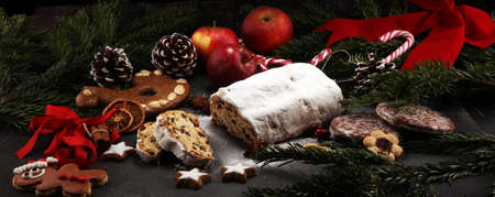 Traditional European Christmas pastry, fragrant home baked stollen, with spices and dried fruit. Sliced on rustic table with xmas tree branches and decorations.