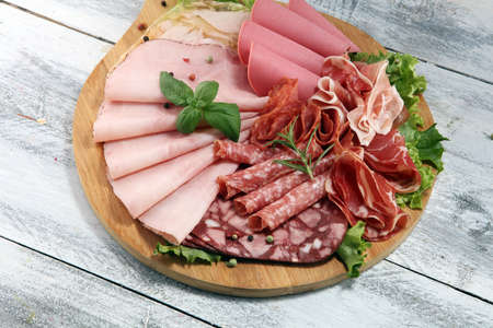 Food tray with delicious salami, pieces of sliced ham, sausage and salad. Meat platter with selection Stock Photo
