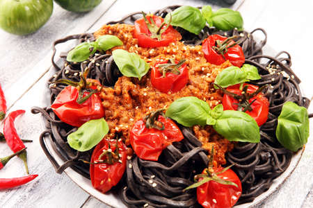 Fresh black tagliolini pasta. Fresh homemade pasta with basil and tomato on the rustic table.