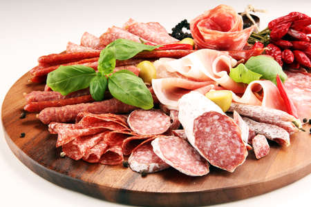 Food tray with delicious salami, pieces of sliced prosciutto crudo, sausage and basil. Meat platter with selection. Stock Photo