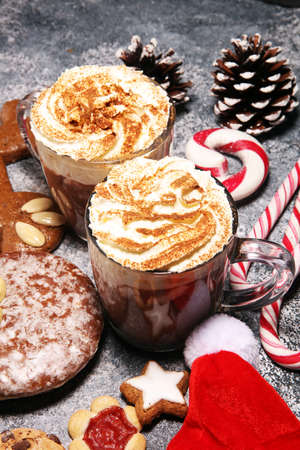 Hot chocolate cocoa with whipped cream and cookies for xmas on table.